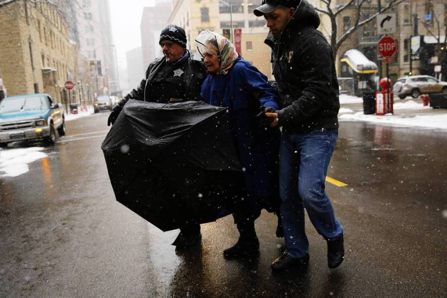 Chicago Police Officer Charlie Bant, left, and passerby Haldo Zamora, right, from East Chicago, Ind., help an elderly woman across the street after she fell in the snow. — Chris Walker, Chicago Tribune, March 5, 2013