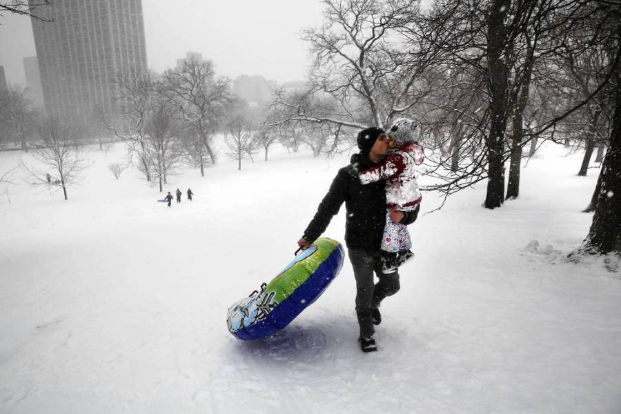 Marius Grigore gives his daughter Ariadna, 4, a big kiss on the cheek as he carries her and their inner tube back up the hill in Lincoln Park to go sledding. — Nancy Stone, Chicago Tribune, March 5, 2013