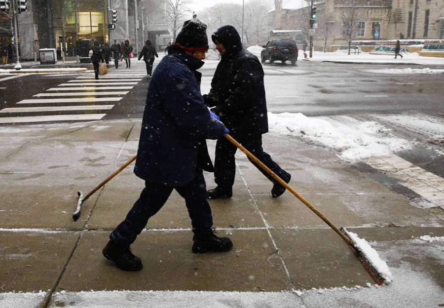 Custodians scrape the walks at Michigan Avenue and Pearson Street. — Chris Walker, Chicago Tribune, March 5, 2013