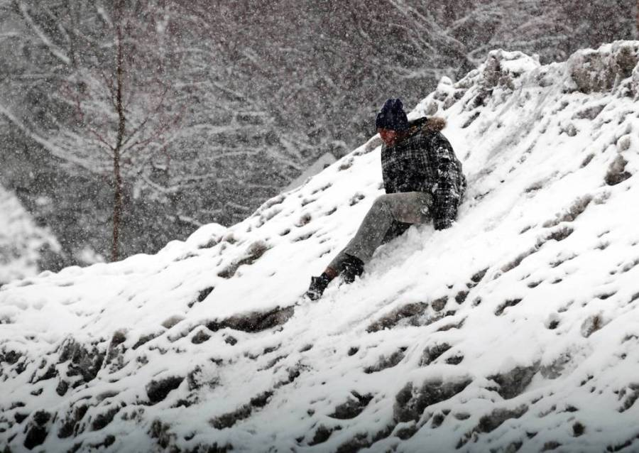 CT WinteQuenton Shears, 14, of Elgin slides down a snow pile as he and a friend make their way to a grocery store in Elgin. — Stacey Wescott, Chicago Tribune, March 5, 2013rStormA.jpg