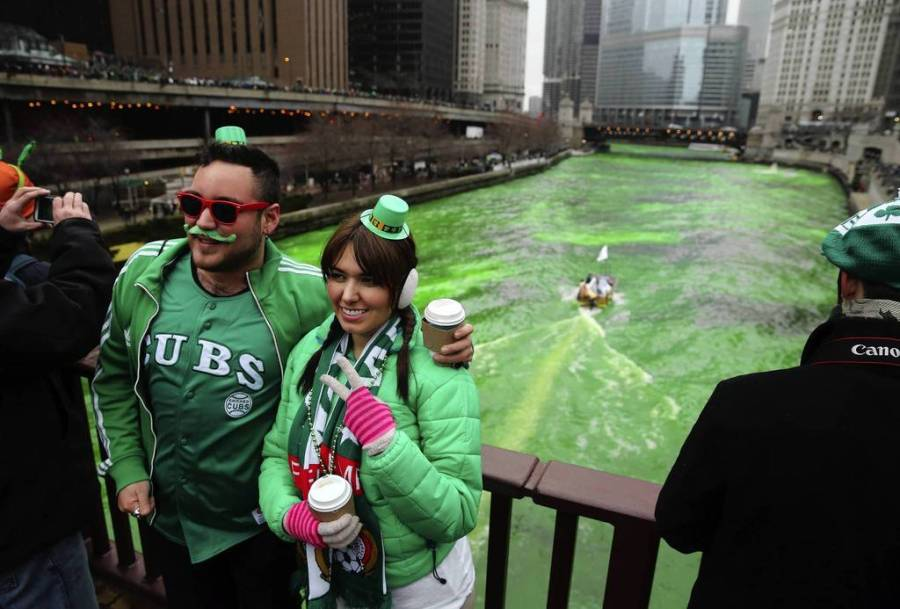 """The dyeing of the Chicago River began at about 10 a.m. as thousands """"ooohed"""" in the frigid temperatures, including Manuel Banuerlos, left, and Charbel Kuri, second from left, as a boat left a trail of lime green dye in the water behind. — Brian Cassella, Chicago Tribune, March 16, 2013"""
