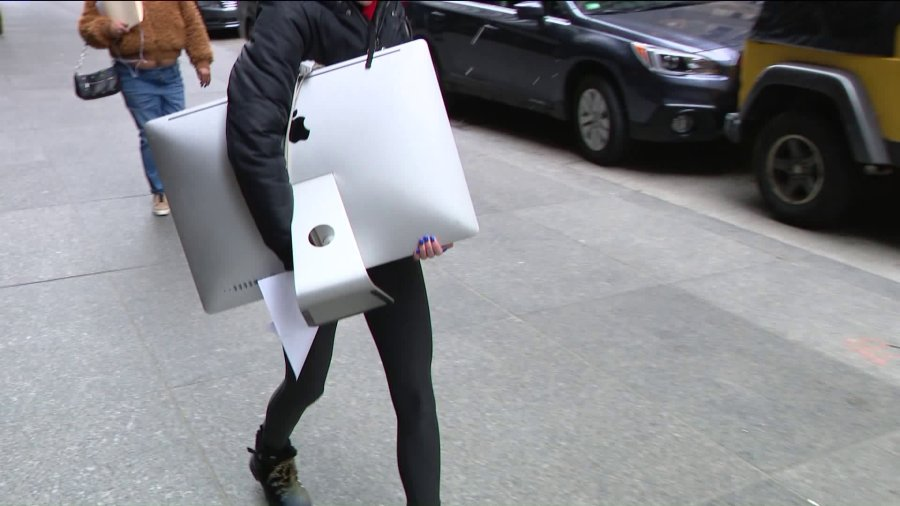 A worker walks with their computer monitor